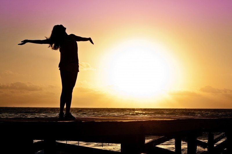 silhouette-of-woman-standing-on-pier-at-sunset